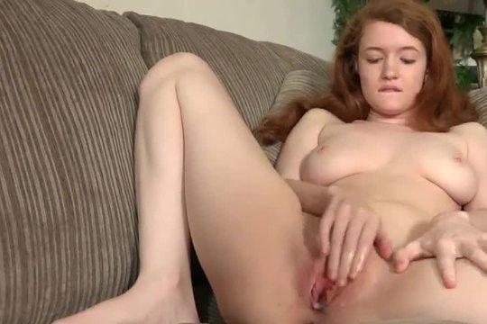 Рыжая малышка с красивой грудью ласкает киску на диване