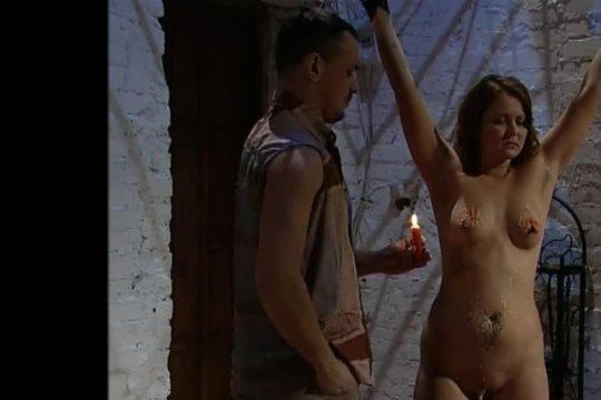 Мужик издевается над стройной рыжей сукой с помощью щипцов и воска, а потом они целуются