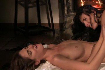 Две красивые лесбиянки блондинка и брюнетка ласкают друг друга на полу у камина