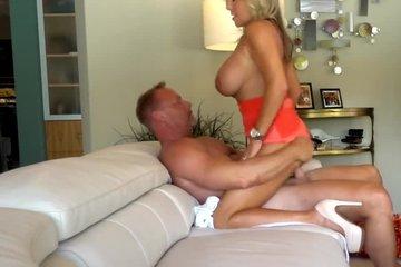 Зрелая блондинка с силиконовыми сиськами и красивой попкой занимается качественным сексом на диване