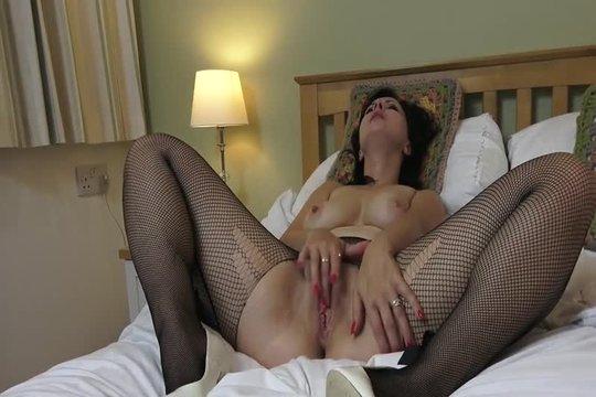 Зрелая брюнетка в чулках мастурбирует бритую киску в спальне